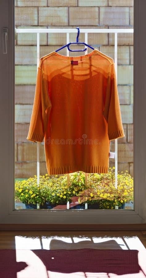 orange Pullover an einem Geländer stockbilder