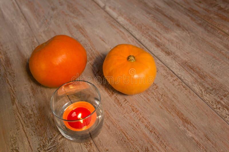 Orange pumkins med den färgrika stearinljuset i exponeringsglaset på träbrädena arkivbild