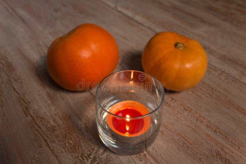 Orange pumkins med den färgrika stearinljuset i exponeringsglaset på träbrädena royaltyfri bild
