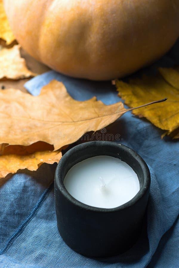 Orange pumpa torra färgrika Autumn Leaves för svart stearinljus för sten vit på den blåa linnetorkduken Hemtrevlig tankfull atmos royaltyfri fotografi