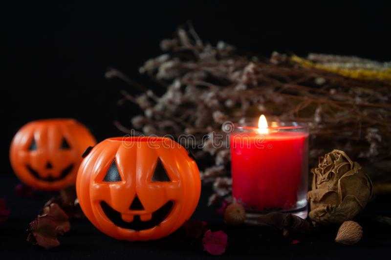 Orange pumpkin as a head with carved eyes and a smile with burning candles on a black background with a garland to the Halloween royalty free stock photo