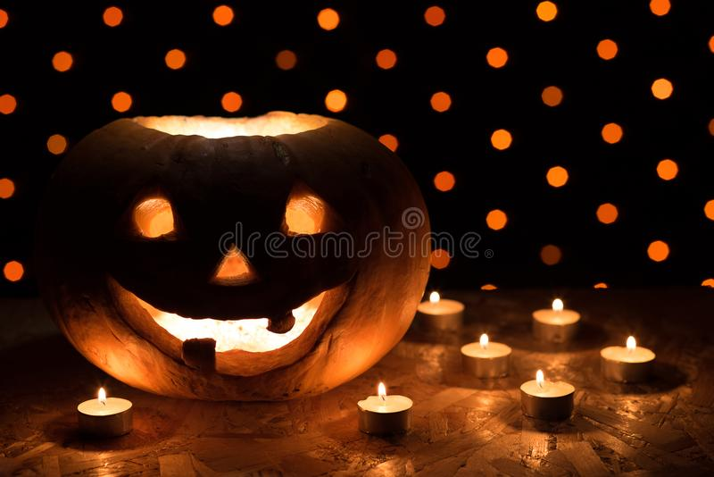 Orange pumpkin as a head with carved eyes and a smile with candles on a black background with a garland to the Halloween party stock photo