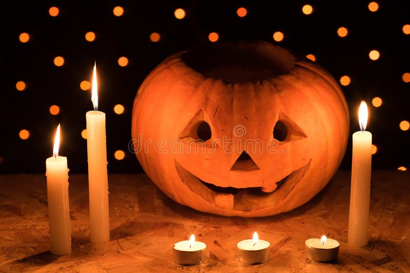 Orange pumpkin as a head with carved eyes and a smile with candles on a black background with a garland to the Halloween party stock photos