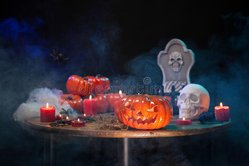 Orange pumpkin carved with scary face for halloween party on a wooden table royalty free stock image