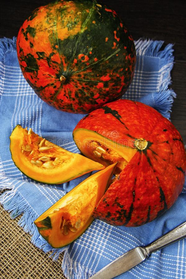 Orange pumpkin hokkaido on a blue linen napkin royalty free stock images
