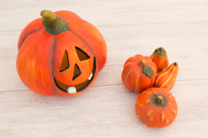 Orange pumpkin lantern with a spooky face smiling on a wooden gr. Ey background stock image