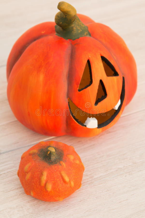 Orange pumpkin lantern with a spooky face smiling on a wooden gr. Ey background royalty free stock photography