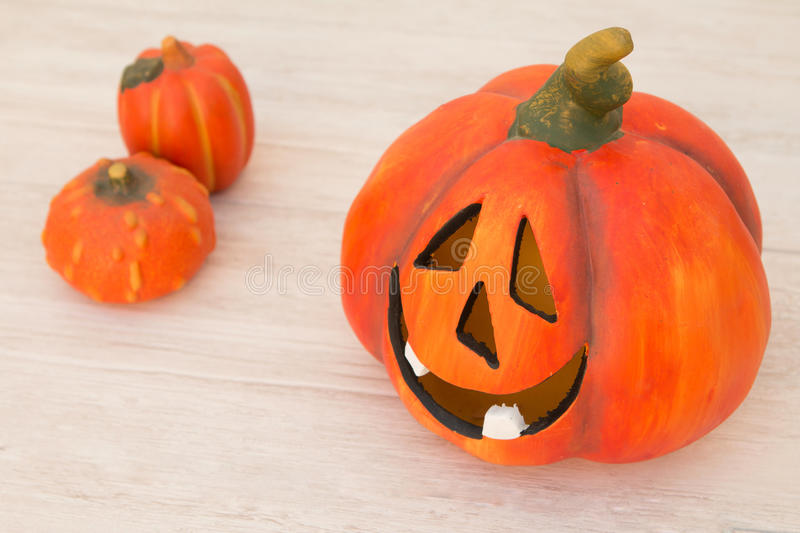 Orange pumpkin lantern with a spooky face smiling on a wooden gr. Ey background stock photo