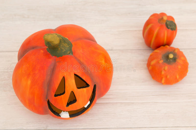 Orange pumpkin lantern with a spooky face smiling on a wooden gr. Ey background stock images