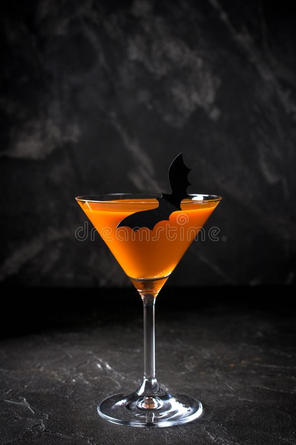 Orange pumpkin martini Halloween drink for party over black background. copy space. Orange pumpkin martini Halloween drink for party over black background with royalty free stock photography