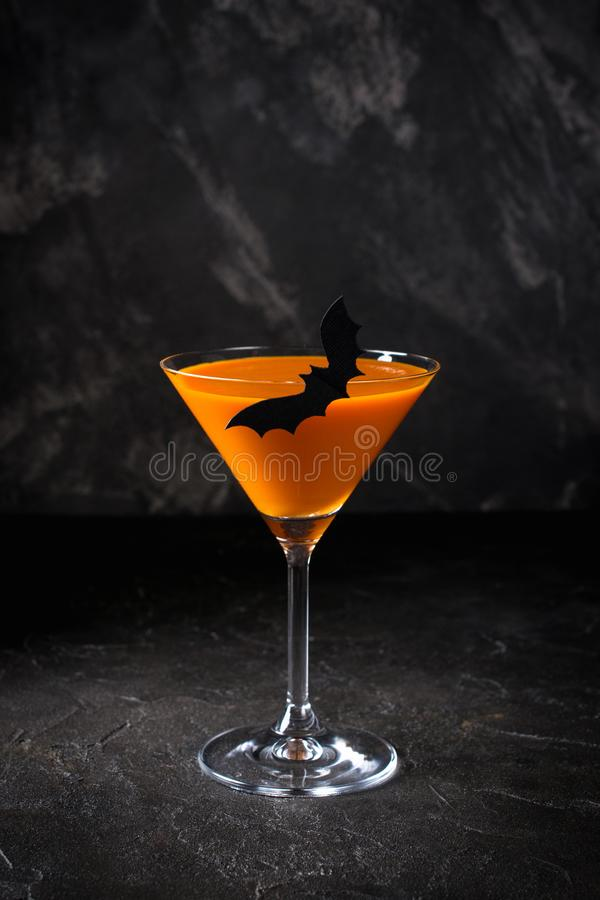 Orange pumpkin  martini Halloween drink for party over black background  with copy space. Orange pumpkin  martini Halloween drink for party over black background stock photography