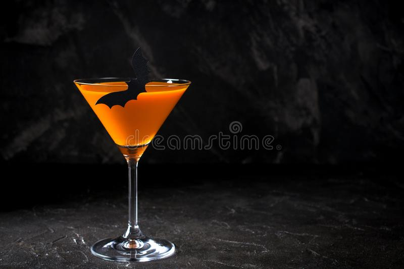 Orange pumpkin martini Halloween drink for party over black background. Copy space. Orange pumpkin martini Halloween drink for party over black background with stock photos