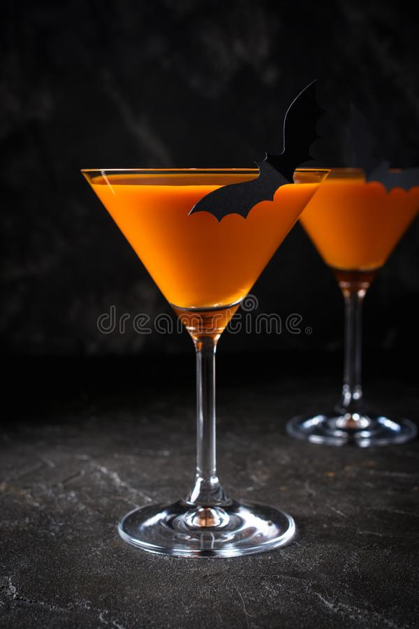 Orange pumpkin  martini Halloween drink for party over black background  with copy space. Orange pumpkin  martini Halloween drink for party over black background royalty free stock images