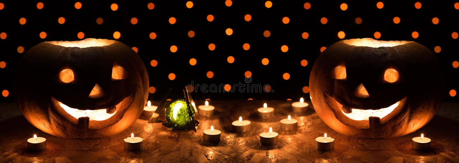 Orange pumpkins as a head with carved eyes and a smile with candles on a black background with a garland to the Halloween party royalty free stock images