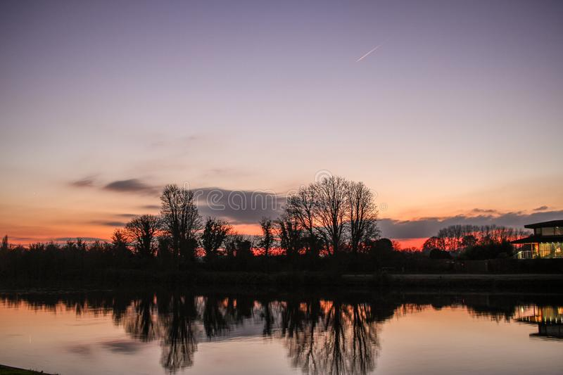 Orange and purple sunset near Kingston upon Thames in England in December. Trees in silhouette reflected in the River Thames. A vignetted clear winter sky royalty free stock photography