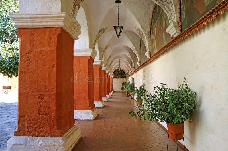 Orange röda korridorkolonner och väggfreskomålningmålningar i kloster av Santa Catalina, historisk plats i Arequipa, Peru royaltyfria foton