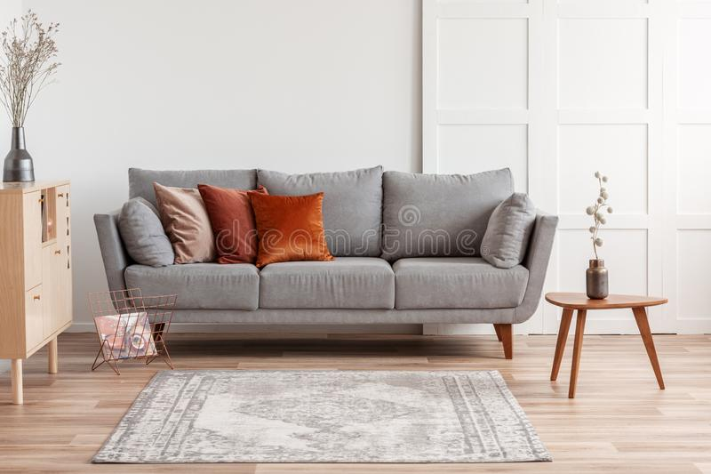 Orange and beige pillows on grey comfortable couch in chic living room interior. Orange, red and beige pillows on grey comfortable couch in chic living room royalty free stock photography