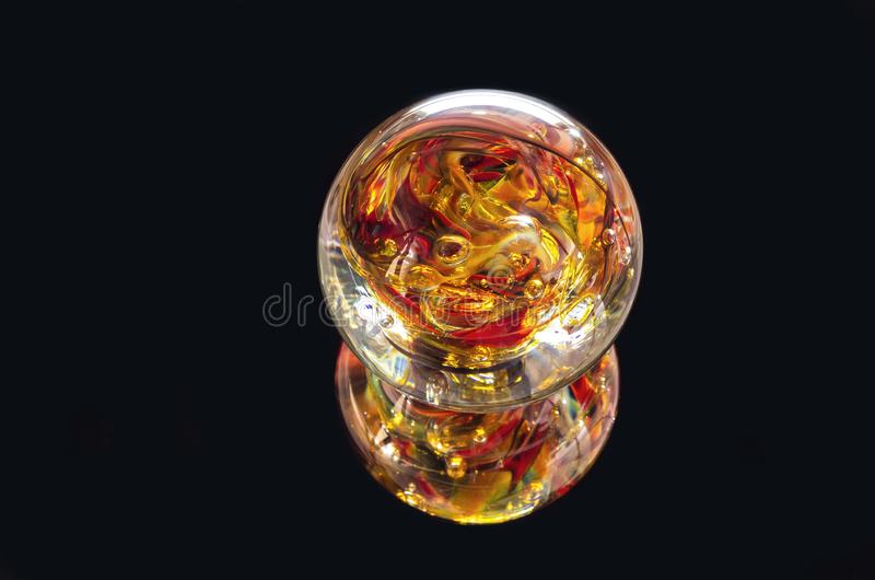 Orange and Red Glass Sphere. Vibrant colored glass sphere and reflection isolated against black stock image