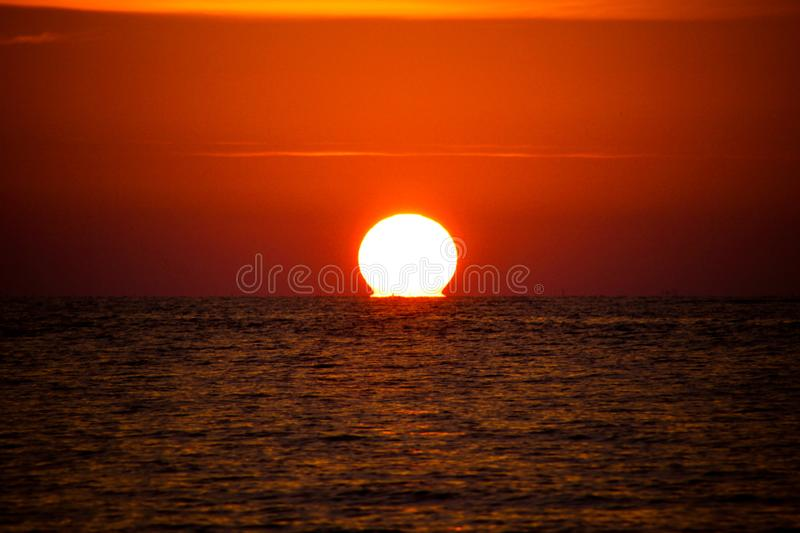 Orange red glowing bright round sun ball melting into the horizon of ocean of tropical island Phuket, Thailand. Orange glowing bright round sun ball melting into stock image