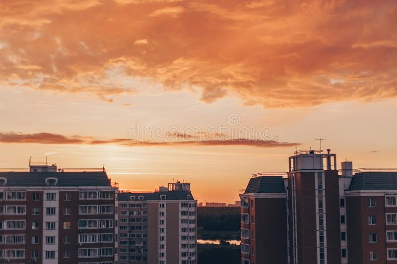 Orange-red sunset with clouds with residential buildings. Orange-red sunset with clouds in summer with residential buildings stock image