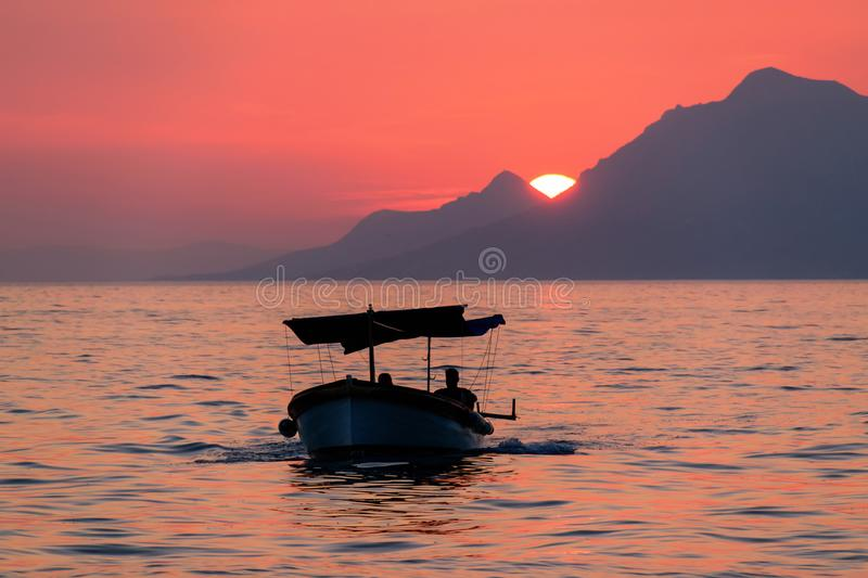 Orange sunset, sea and boat in Croatia royalty free stock photo