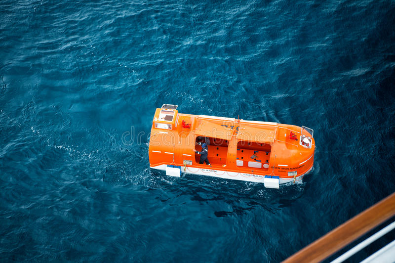 Orange rescue, lifeboat for emergency evacuation with people on water stock photo