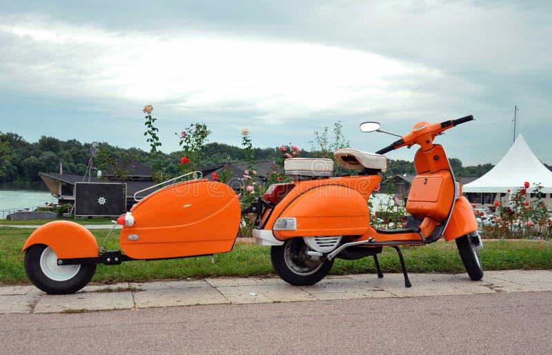 Orange retro vespa royaltyfri fotografi