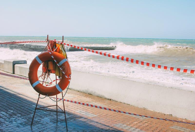 Orange Rettungsleine auf dem Hintergrund des geschlossenen leeren Strandes im Sturm stockfotografie