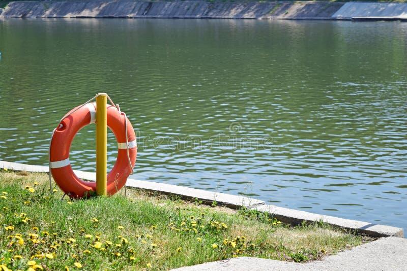 Orange Rettungsleine nahe dem Wasser Das Rettungsleine ` s auf dem Haken lizenzfreie stockfotos