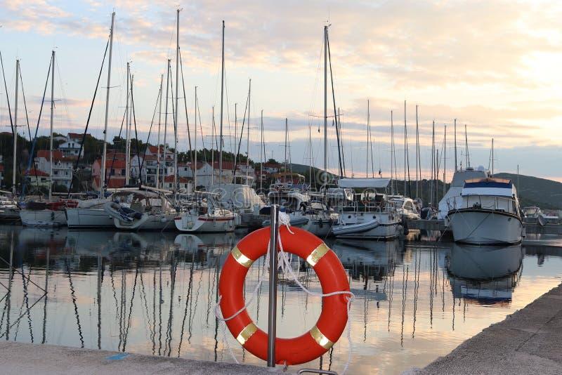 Orange Rettungsring auf dem Pier im kroatischen Jachthafen gegen den Hintergrund von Segeljachten Sicherheit auf dem Wasser und d stockbilder
