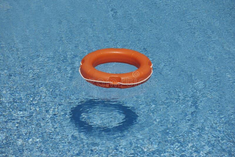 Orange Rettungsringe im blauen Wasser stockfotos