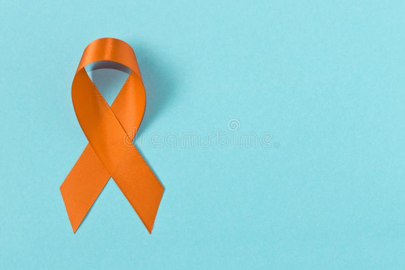 Orange ribbon on blue background . Healthcare and medicine concept. Multiple Sclerosis awareness. Leukemia awareness. Empty text. Space royalty free stock images