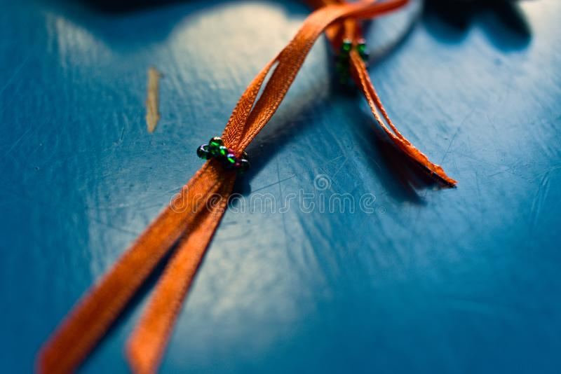 Orange ribbon on a blue background. royalty free stock photography