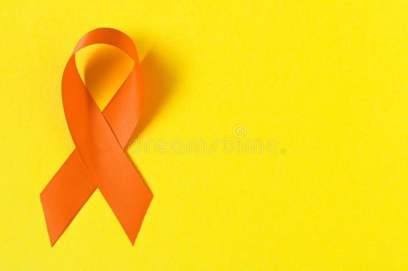 Orange ribbon. Healthcare and medicine concept. Multiple Sclerosis awareness. Leukemia awareness. Empty text space.  royalty free stock photos