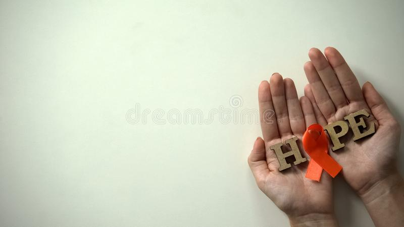 Orange ribbon and hope word in hands, leukemia awareness campaign and treatment. Stock photo royalty free stock photo