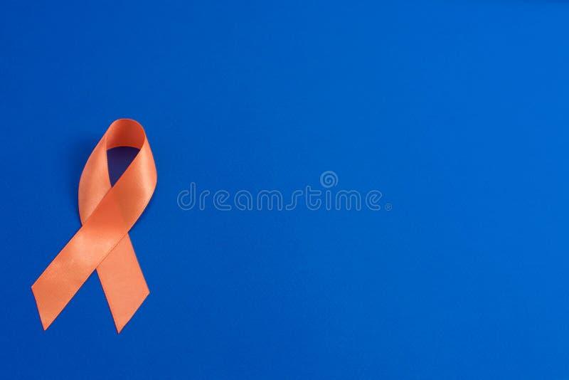 Orange ribbon. Leukemia awareness. healthcare and medicine concept. Orange ribbon on blue background. healthcare and medicine concept. Multiple Sclerosis stock photo