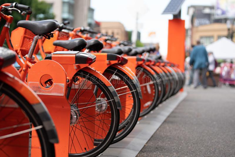 Orange ride sharing bicycles. Stacked parked in downtown Portland stock photo