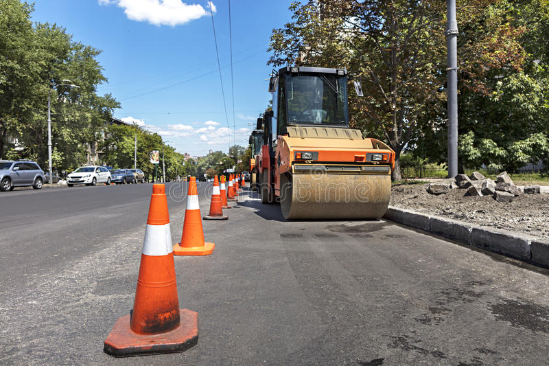 Orange road cones protect heavy wheel compactors along the edge of the city street road stock photos