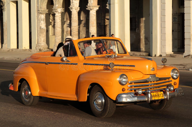 Orange roadster on the boulevard. HAVANA, CUBA, FEBRUARY 15, 2014 : Classic old American car in the streets of Havana. Classic cars are still in use in Cuba and royalty free stock photography