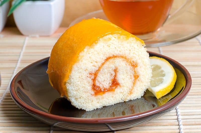 Orange Rollenkuchen in der Platte mit orange Scheibe lizenzfreies stockfoto