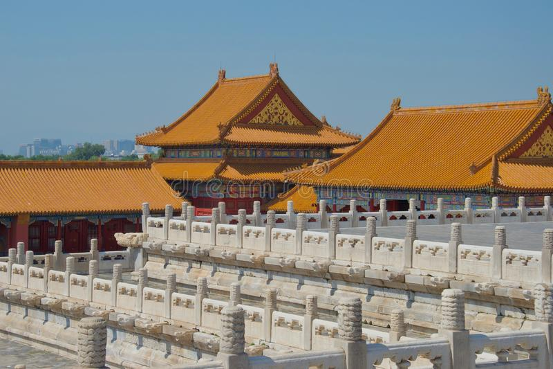 Orange roofs of traditional chinese buildings with white marble pillars in foreground stock photos