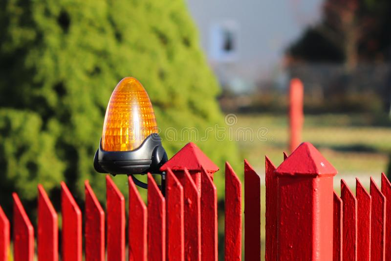 Orange room alarm light located on a brick fence post. Intercom apartment building at the entrance to a private protected area. Ha. Zard alert. Intercom for door royalty free stock images