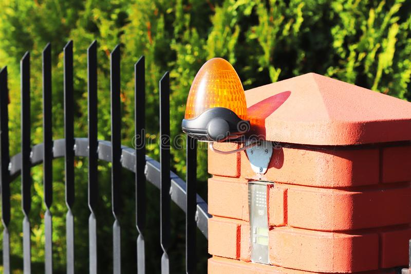 Orange room alarm light located on a brick fence post. Intercom apartment building at the entrance to a private protected area. Ha. Zard alert. Intercom for door royalty free stock photos