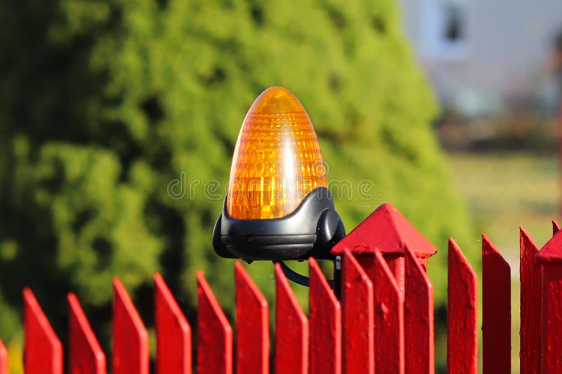 Orange room alarm light located on a brick fence post. Intercom apartment building at the entrance to a private protected area. Ha. Zard alert. Intercom for door royalty free stock photography