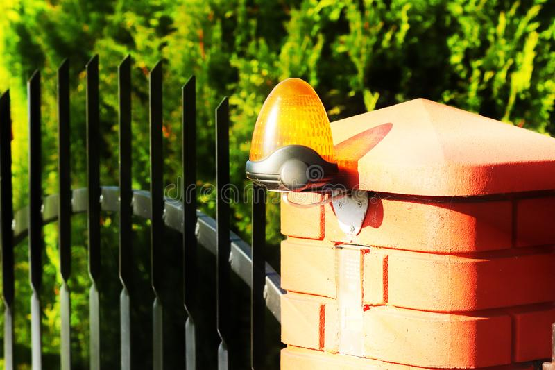 Orange room alarm light located on a brick fence post. Intercom apartment building at the entrance to a private protected area. Ha. Zard alert. Intercom for door stock photos