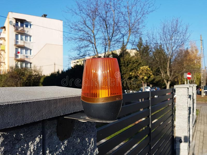 Orange room alarm light located on a brick fence post. Intercom apartment building at the entrance to a private protected area. Ha. Zard alert. Intercom for door royalty free stock photo