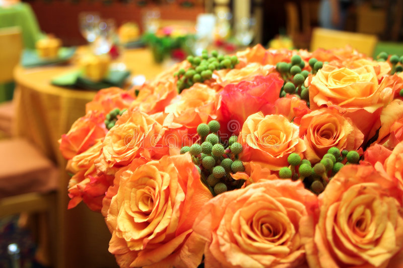 Orange roses. In a lush bouquet in a wedding reception venue royalty free stock images