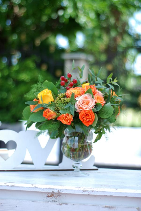 Orange Roses in Clear Glass Vase on White Table with Blurred Green Garden Background. Floral Arrangement. Spring or. Orange Roses in Clear Glass Vase on White stock photos