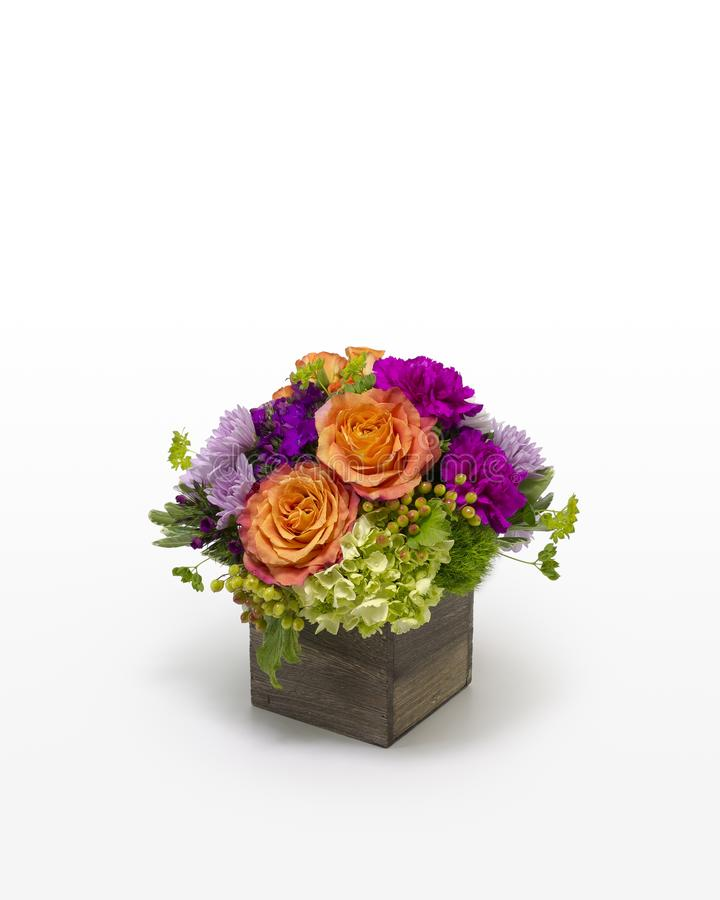 Colorful orange and green floral arrangement in a wood box. royalty free stock image