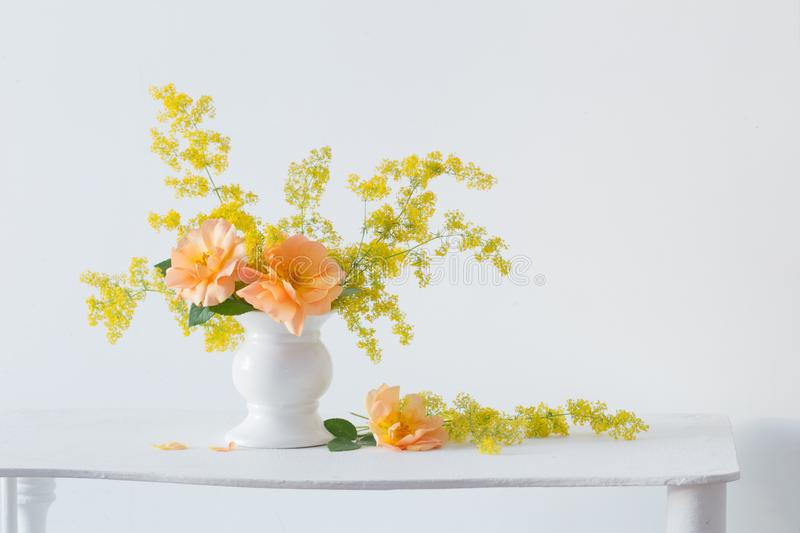 Orange roses with wild flowers in bouquet in white vase royalty free stock photos